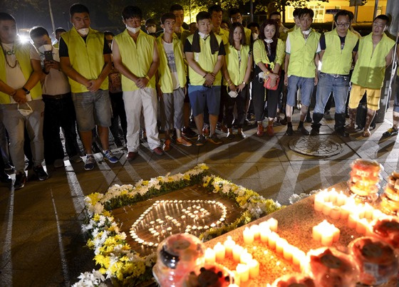 Residents and volunteers attend a candlelight vigil to mourn the victims of Wednesday night's blast