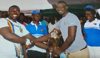 Michael Nkansah-Boateng presenting the trophy to Isaac Oteng, captain of Noka FC