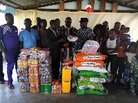 Nathan Gyasi in smock with his family members presenting the items to Rev Sakyi