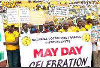 National Vocational Training Institute staff holding placards at last year's May Day parade