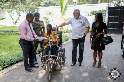 Former President Jerry John Rawlings with Emmanel Ofoe, the physically challenged street beggar
