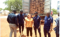 Helen Huang in the company of some police officers and the container loads of rosewood in Tamale