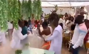 A picture of the groom dancing with his guest whiles his friends cheer him up