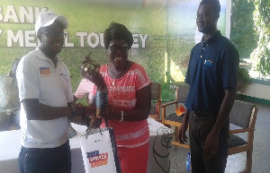 Lady Capo (middle) receiving her prize from an official of Access