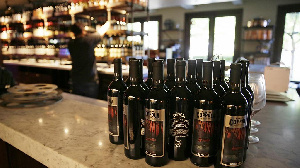 Bottles of Apocalypse Now Red Blend wine are seen on a tasting bar counter