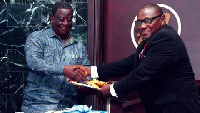 Roads Minister , Kwasi Amoako-Atta receiving the first copy of the book from Dr. Samuel Nikoi