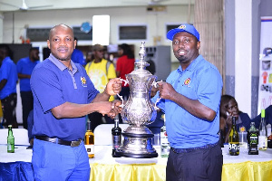 Appiah(left) representing the winner's trophy to Antwi