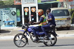 Police officers on motor-bike flout social distance directive. Photo Vincent Dzatse