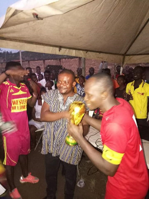 Matthew Ayeh presenting the trophy to the winners