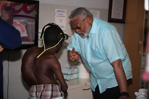 Former President Jerry John Rawlings interacting with a deformed patient