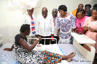 Akufo-Addo and some party leaders interacting with a mother at the hospital