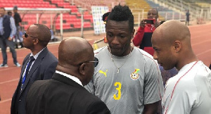 President Akufo-Addo interacting with Asamoah Gyan, looking on is Dede Ayew