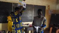 An official of Autonomous National Electorial Commission (CENA) raises a ballot paper