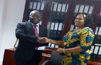 Siengui Apollinaire (left) receiving the documents from Ifeyinwa Ikeonu