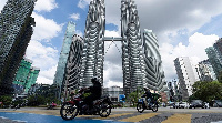 Motorists ride past wearing face masks in front of the Twin Towers in Kuala Lumpur, Malaysia (AP)
