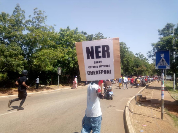 A youth holding a placard that reads 'North-East Region can be created without Chereponi' on it