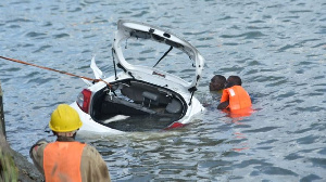 Rescuers retrieve a car from the ocean after it plunged into the Makupa Causeway