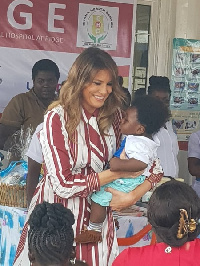 US First Lady, Melania Trump carrying a child during her donation in Accra