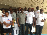 Mr Evans Ayai displaying the May 1 trophy as he poses with Mr Richmond Quarcoo (second right)