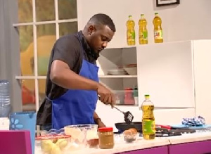 Actor John Dumelo cooking on 'Dining with Cooks and Braggarts' hosted by Yvonne Okoro