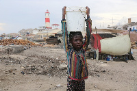 A child carries water from the shore of Jamestown in Accra
