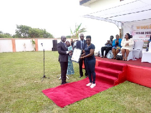 Deputy Attorney General, Godfred Dame presenting the citation to Mercy Tagoe