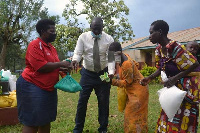 The girl and her mother receive an assortment of items from Genevieve Bamwidhukire.