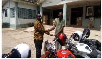 Mr Kena presenting the bikes to Agric Director