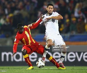 Jonathan Mensah of Ghana is tackled by Clint Dempsey of USA