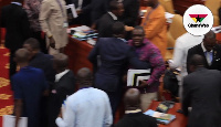 Sam George being restrained by other minority members in Parliament on Thursday