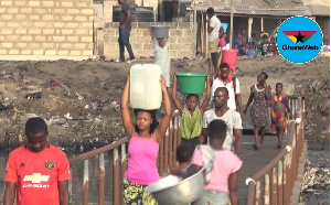Residents cross a bridge before they can access potable water