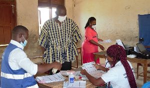 Mr. Robert Apechira Aloo interacting with EC staff at a centre in Paga
