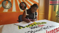 Nana Oye Lithur signing the petition