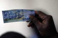 Man holds up 5 cedi note