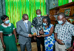 Speaker Alban Bagbin receiving a plaque from the group