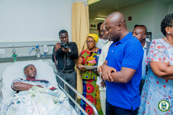 Mayor Sowah (in blue) visits a patient in his ward at the Greater Accra Regional Hospital