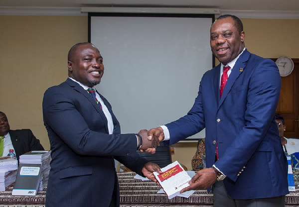 Mr Ebenezer Akyeampong of Heritage Bank presenting a copy of the book to Education Minister