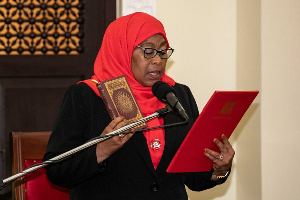 New Tanzanian President Samia Suluhu Hassan holds the Koran during the swearing-in ceremony