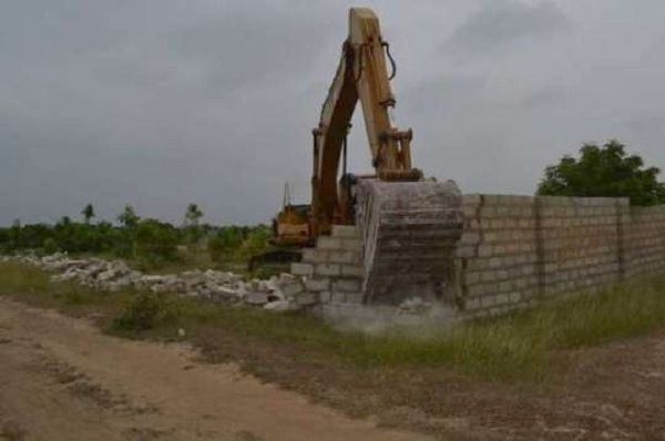 A bulldozer bringing down the storey building and other structures on the land.