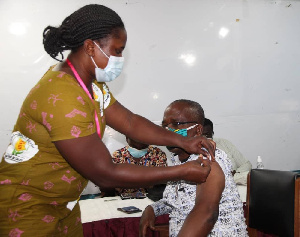 A nurse administering an injection on an individual