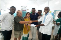 Mr Azongo (L) receiving cash donation from officials of the NGO at the Paediatric Department