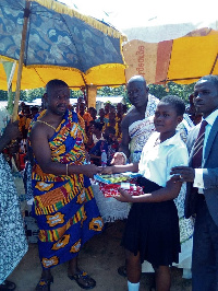 Appianyinasehene (L) presenting an item to one of the students. With him the is the head teacher