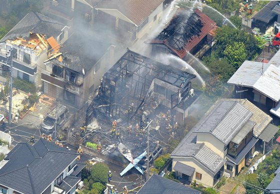 An aerial view shows debris of a crashed light plane (bottom C) and burning houses