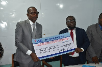 Affail Monney and Faris Attrickie displaying the dummy cheque after the signing ceremony