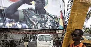 A sun-glasses seller walks past a billboard showing junta leader, Colonel Mamady Doumbouya