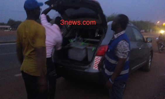 The ballot boxes being put in the booth of the car by the electoral officers.