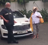Ex president JJ Rawlings poses by the car with an unidentified woman