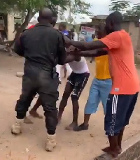 A police officer being attacked by some residents of Amasaman in Accra