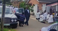 The pastor walks majestically from his car to the Church premises with his members kneeling down