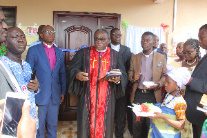 Apostle Richard Buafor [in cassock] being assisted by others to dedicate the clinic